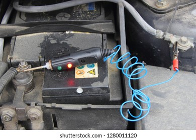 Close up old black car battery accumulator with electrolyte acid drips and probe tester with lamp - repair of vehicle electrical equipment