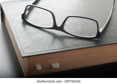 Close up of an old book and reading glasses