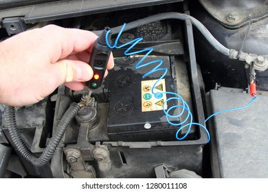 Close up old car battery with electrolyte acid drips and probe diagnostic tester lamp in serviceman hand - repair of vehicle electrical equipment