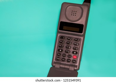 close up of an old cell phone on teal background Space on sides for text