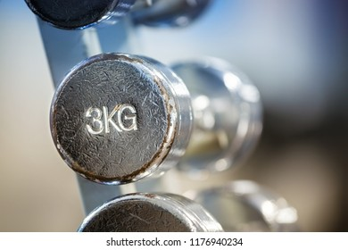 Close up of old chrome 3kg dumbbell in a rack.