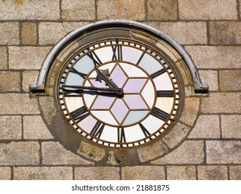Close up of an old clock face on a stone wall.