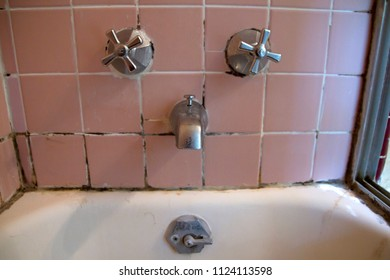 Close up of an old, dirty, porcelin bathtub, faucets and grout with mildewed ceramic tiles