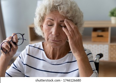 Close up old disabled woman sit in wheel chair taking off glasses closed eyes reduces eyestrain suffers from headache feels exhausted. Poor vision, age-related eye problems, glaucoma, dry eyes concept