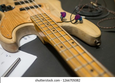 close up old electric wood bass 4 strings with ear phone and paper song and pen