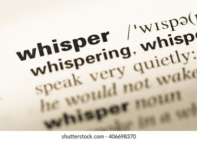 Close up of old English dictionary page with word whisper