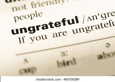 Close up of old English dictionary page with word ungrateful