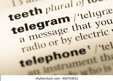 Close up of old English dictionary page with word telegram