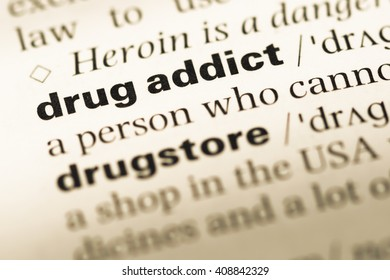 Close up of old English dictionary page with word drug addict