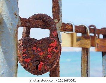 close up of an old heart shaped red rusty padlock chained to a railing with others in a lone out of focus on a bright sunlit summers day