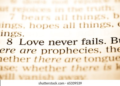 "Close up of old Holy bible book, The word ""Love never fails""."
