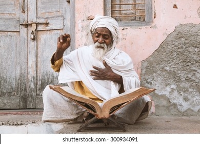 Close up of an old indian sadhu (saint) sitting and reading sacred texts near the temple.