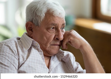 Close up old male put head on hand lost in sad thoughts memories, widower yearning for his wife feels lonely in nursing home, 70s senior man has senile disease geriatric medicine end of life concept