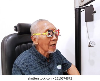 Close up of old man using a glasses phoropter while checking his myopic eyes at ophthalmologist