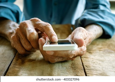 Close up of a old man using mobile smart phone
