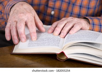 Close up of old man's hands holding a book
