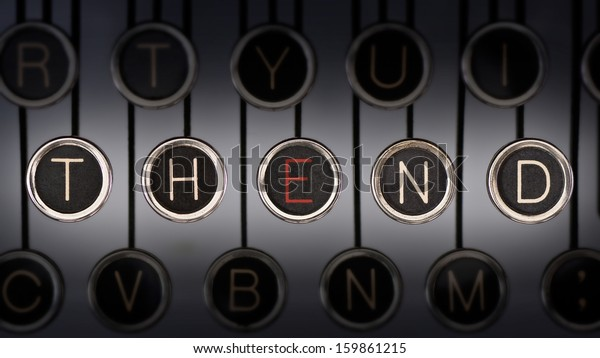 """Close up of old manual typewriter keyboard with scratched chrome keys that spell out """"THE END"""". Both words share the letter, 'E', highlighted in red.  Lighting and focus are centered on """"THE END"""""""