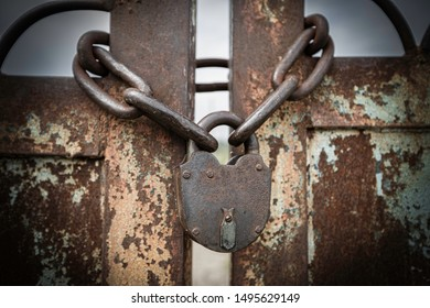 Close up of old metal lock and chain on the ground.