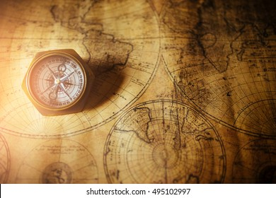 Close up of an old nautical compass on vintage map. with sunshine