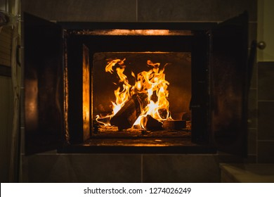 Close up of an old open brick stove or bread oven in an old house. Open fire with wood logs in  a bread oven or a furnace. Doors of a furnace are open