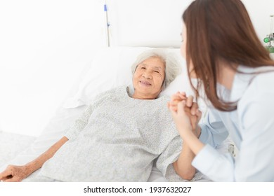 close up old people, old asian patient sick and admit in hospital, young asian female visiting old female, they holding hands together, they feeling happy and smile, elderly healthcare