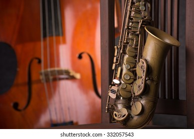 close up old Saxophone and blur double bass background on low key image