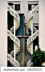 Close up of old stone spiral staircases on the exterior of traditional Singapore shophouse in Little India in vertical view