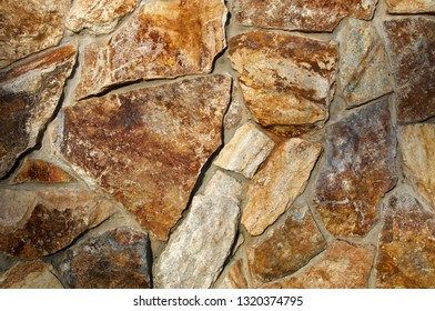 Close up of old stonewall with rocks of different shapes and sizes with deep shadows from morning sunlight..
