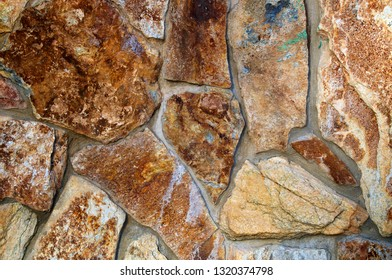 Close up of old stonewall with rocks of different shapes and sizes.