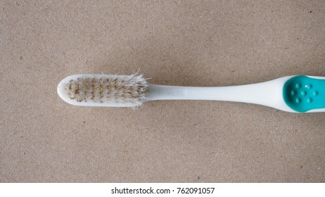 close up of old used toothbrush on brown paper
