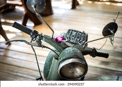Close up of old vintage green scooter parked on patio with orchid flower sitting on top