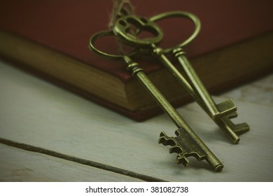 Close up of old vintage keys and book on a rustic background. Vintage filter applied.