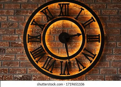 Close up old vintage retro style metal wall clock over background of grunge brick wall - loft style
