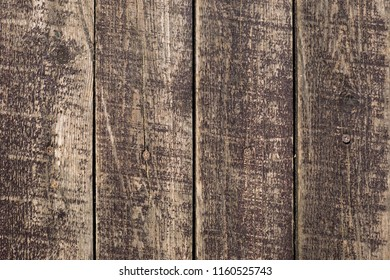Close up of old washed out weathered stripped brown wooden planks with scratches and nails. Abstract natural texture background