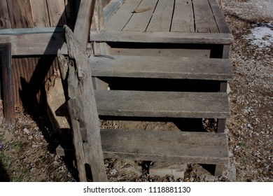 Close up of old, weathered steps leading to a wood porch