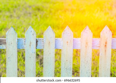 Close up old white fence in garden with sunrise