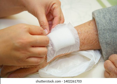 Close up old woman wrinkled skin hand, upper limb or arm to the wounded waiting for nurse treatment on wound dressing a bloody and brine of patient on white background.