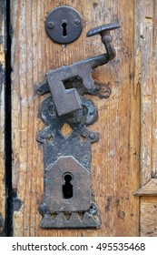 Close up of an old wooden front entrance with decorative antique door handle