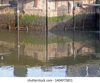 a close up of old old wooden lock gates in the clarence dock area of leeds reflected in the water