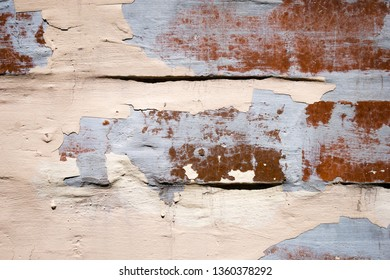 Close up of old worn cracked wall with peeling paint and plaster. Abstract texture background