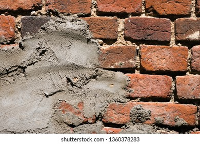 Close up of old worn grunge red brick wall with layer of putty. Rough surface. Abstract texture background