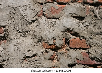 Close up of old worn grunge red brick wall with layer of plaster. Rough surface. Abstract texture background