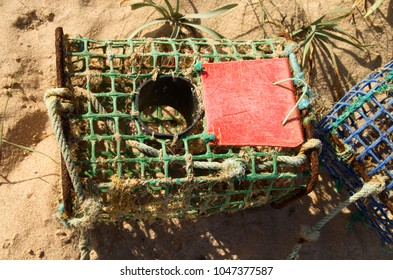 Close up of an old and worn-out, artisanal, crab trap made of iron and colored plastic materials. Vila Nova de Milfontes, Portugal.