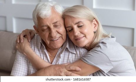 Close up older husband and wife hugging with closed eyes, senior family enjoying tender moment, adult middle-aged daughter embracing mature father, expressing love and gratitude, two generations
