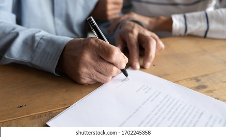 Close up older man putting signature on legal documents, mature couple, wife and husband making purchasing or investment deal, taking loan or buying new house, senior male signing contract