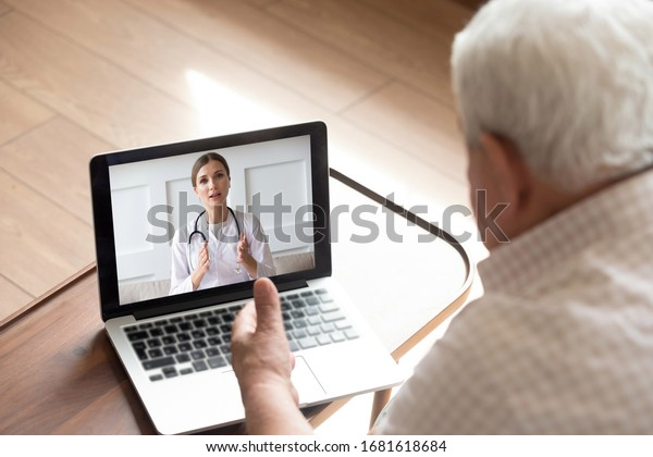 Close up older man talking with doctor by video call, using medical apps on laptop, service, friendly young woman wearing white uniform coat with stethoscope consulting mature senior patient online