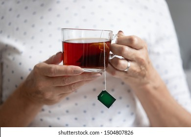Close up older woman holding glass cup of black tea with tea bag inside in hands with manicure, mature female relaxing at home, drinking enjoying hot beverage in mug in the morning