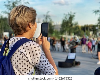 Close up of an older woman with short blond hair and a backpack using her phone to take a picture of street musicians outside during the day in Moscow, Russia.