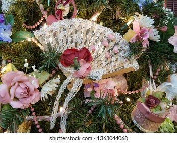 close up of old-fashioned lace fan with rose bouquet ornament on green Christmas tree