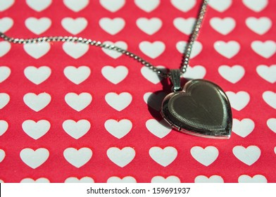 Close up of an old-fashioned locket against a Valentine heart background